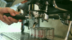 Barista making a shot of coffee espresso and streaming milk - stock footage
