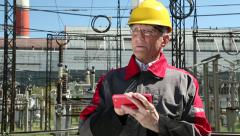 Power engineering specialist with red smartphone at electropower station Stock Footage
