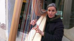 Harp player plays his harp near accademia bridge in Venice Stock Footage