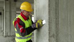 Worker with putty knife at construction site Stock Footage