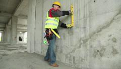 Worker with yellow level at building site - stock footage