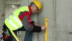 Worker in yellow hard hat with level at building plot - stock footage