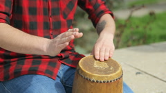 Close-up of a guy in a plaid shirt beating on a drum Stock Footage