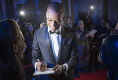 Well dressed celebrity signing autograph on red carpet - stock photo