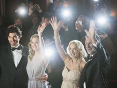 Well dressed celebrity couples waving to paparazzi at red carpet event Kuvituskuvat