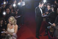 Well dressed celebrities signing autographs on red carpet - stock photo