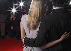 Close up rear view of celebrity couple hugging for paparazzi on red carpet Kuvituskuvat