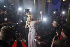 Celebrity couple waving to fans and paparazzi on red carpet Kuvituskuvat