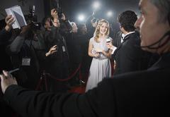 View over bodyguard's shoulder of celebrity being interviewed on red carpet Stock Photos