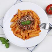 Italian cuisine penne Rigate Bolognese sauce noodles pasta meal from above Stock Photos