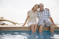 Stock Photo of Senior couple dipping feet in swimming pool