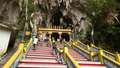 Hard way up to Batu Caves, long stairs and people climb up, stalactite vault Stock Footage