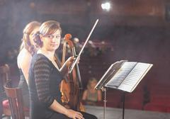 Violinists preparing for performance on theater stage - stock photo