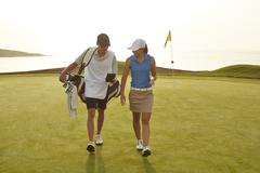 Golfer and caddy walking on golf course Stock Photos