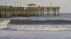 Slow motion waves curling in front of pier Stock Footage