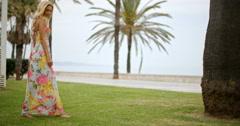 Woman in Long Sun Dress Walking Through Park Stock Footage