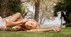 Woman Wearing Sun Dress Lying on Side on Grass Stock Footage