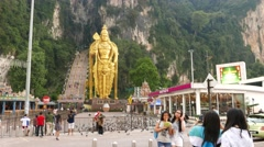 Group of asian girls pose against Murugan statue, Batu Caves square Stock Footage