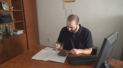 Junior young accountant working at the office compute and write in book register Stock Footage