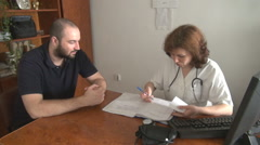 Visit at doctor office white patient talking with woman medic patient file check - stock footage