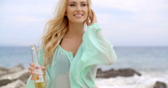 Blond Woman Holding Bottle of Beer on Beach Stock Footage