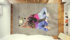 High shot of two teenagers taking selfie in living room lying on the floor Stock Footage