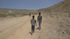Two boys walking on a country road in Haiti Stock Footage