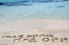 TAKE SOME TIME OFF written on sand on a beautiful beach - stock photo