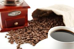 Coffee cup with winnower and sack of coffee beans on white - stock photo