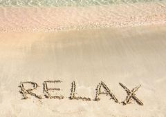 Relax word written in the sand, on a beautiful beach with clear blue waves Stock Photos