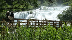 Visitor crossing the bridge and photographing Krka waterfall Stock Footage