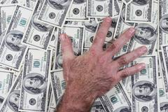 Man's hand which lays on the dollars Stock Photos