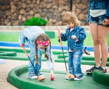 Mother and daughter playing golf on a golf course Stock Photos