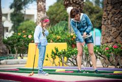 Mother and daughter playing golf Stock Photos