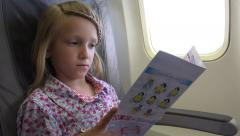 4K Passenger Girl in Plane, Tourist Child, Kid, Aboard Reading Flying Airplane Stock Footage