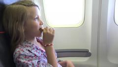 4K Young Girl in Plane, Pensive Thinking, Hungry Kid Child Eating in Airplane Stock Footage