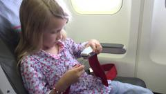 4K Young Girl in Plane Learning Safety Belt Seat Belt Child Travelling Airplane Stock Footage