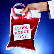 Stock Photo of doctor holding a blood bag with the text blood donor day