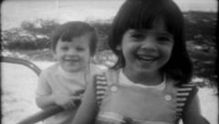 2169 - children play on ride at local park - vintage film home movie Stock Footage