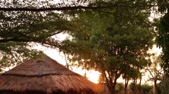 Thatched roof hut sunset rain - stock footage