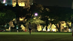 Footballers play nighttime game near St. Andrews Anglican Cathedral Stock Footage