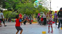 KUALA LUMPUR, MALAYSIA - CIRCA FEB 2015: Children playing with bubbles at Tit Stock Footage