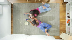 Girls at home playing on the floor with cell phone high shot Stock Footage