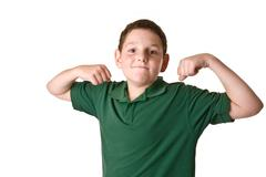 Young boy in a green polo shirt flexing - stock photo