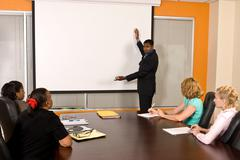 Business Meeting with gentleman gesturing to projector screen - stock photo