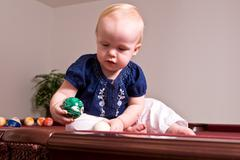 Young child sitting on a billiard table playing Stock Photos