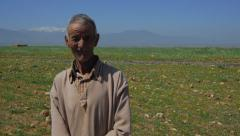 Berber cheep shepherd portrait with altlas mountains in the background Stock Footage