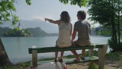SLOW MOTION: Girlfriend and boyfriend sitting on bench by the lake before SUPing Stock Footage