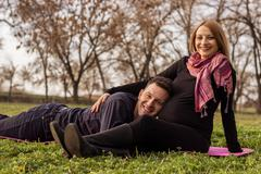 Stock Photo of Pregnancy. Mother and father in park.