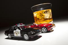 Police and Sports Car Next to Alcoholic Drink Under Spot Light. - stock photo